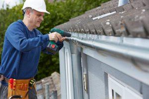 man repairing gutters