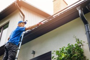 contractor inspecting a homeowner's gutters