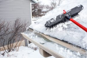 frozen gutters on a house with a roof rake next to them