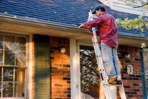 a homeowner inspecting the gutters on their house